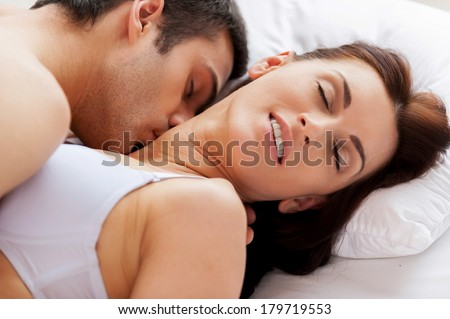 I love him kissing me! Beautiful young loving couple having sex while lying in bed - stock photo
