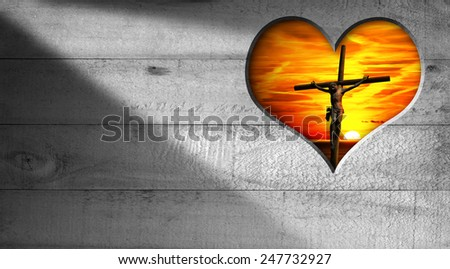 I Love Jesus - Crucifixion at Sunset. Wooden grey background with a hole in the shape of heart with Jesus crucified and a beautiful sunset with cloudy sky - stock photo