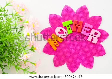 I love mom concept. Mother made from alphabet on pink paper with flower. - stock photo