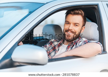 I love my car! Handsome young man driving his car and smiling at camera - stock photo