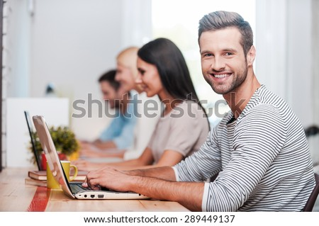I love my job! Group of cheerful business people in smart casual wear working at their laptops while handsome man looking at camera and smiling - stock photo