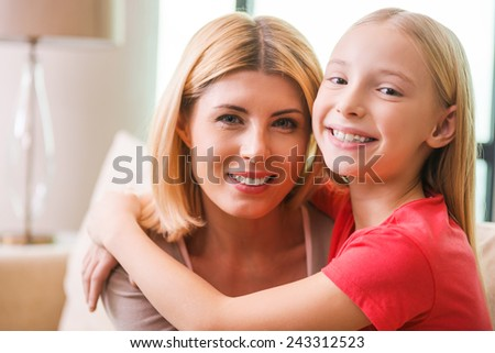 I love my mom! Happy mother and daughter bonding to each other and smiling while sitting at home together - stock photo
