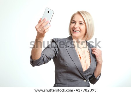 I love selfie! Beautiful woman holding camera and making selfie and smiling while standing against white background - stock photo