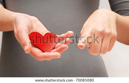I love you concept, womens hands holding a heart and pointing in your direction - stock photo