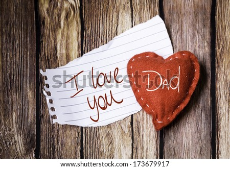 I Love You Dad written on a peace of paper and a heart on a wooden background - stock photo