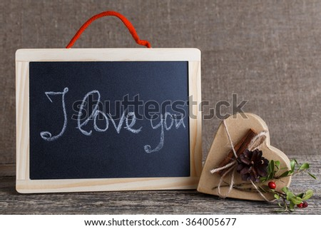 I love you handwritten on black chalkboard with gift box. - stock photo