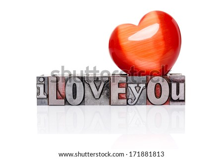 I Love You in old mixed font metal letterpress blocks with a red heart gemstone on top, isolated on a white background. - stock photo