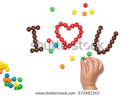 I LOVE YOU of the red and brown chocolate coated candy with children's hand - stock photo