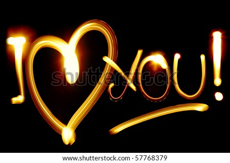 I LOVE YOU phrase created by light over black background - stock photo