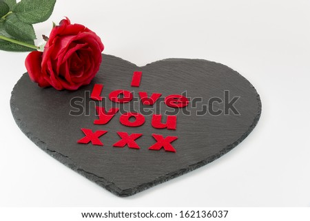 I love you with a red rose on a heart shaped slate with a white background - stock photo