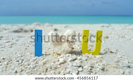 I love you word and heart shape coral and gold ring with the white sand beach and blue sky background - stock photo