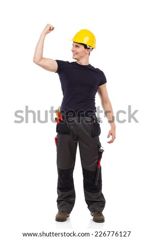 I made it! Shouting construction worker standing with one arm raised and flexing muscles. Full length studio shot isolated on white. - stock photo