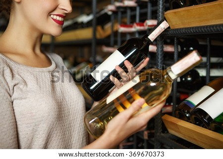 I need both! Cropped closeup of a smiling woman holding two bottles of wine choosing - stock photo