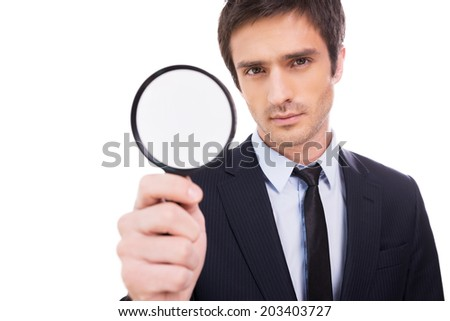 I need details! Concentrated young man in formalwear holding magnifying glass and looking at camera while standing isolated on white background  - stock photo