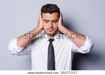 I need silence. Frustrated young man in shirt and tie covering ears with hands and keeping eyes closed while standing against grey background - stock photo