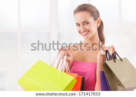 I need some retail therapy. Attractive young woman holding shopping bags and smiling at camera - stock photo