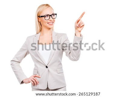 I recommend you this! Confident mature businesswoman pointing away and smiling while standing against white background - stock photo