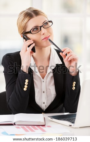 I think it is a good idea. Thoughtful mature woman in formalwear talking on the mobile phone and touching chin with pen while sitting at her working place - stock photo
