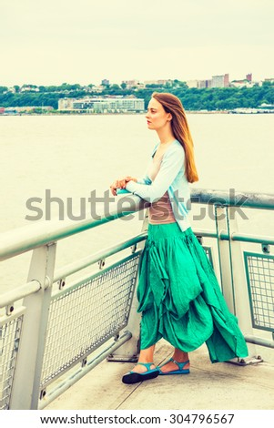 I waiting for you. American college student wearing light blue cardigan, green skirt, sandals, standing by metal fence by Hudson River in New York, opposite New Jersey, holding book, looking forward. - stock photo