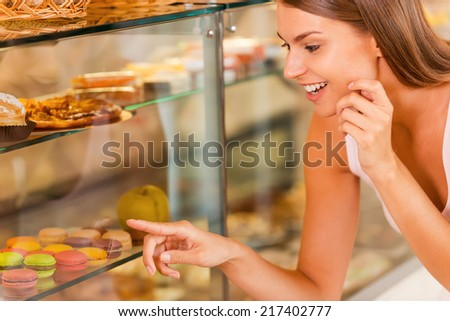 I want them all! Beautiful young woman choosing cake in candy shop  - stock photo