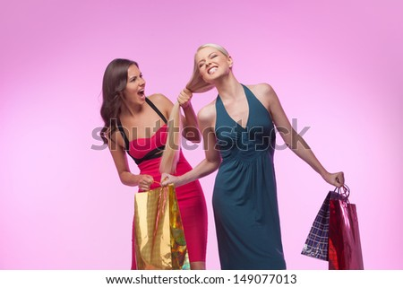 I was the first! Two furious women with shopping bags fighting while isolated on coloured background - stock photo