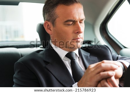 I will be in time. Confident mature businessman looking at his watch while sitting on the back seat of a car  - stock photo