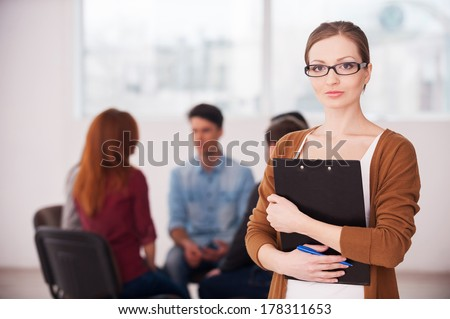 I will help you to solve your problems. Confident woman in glasses holding clipboard and looking at camera while group of people sitting on background - stock photo