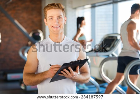 I will make you healthy! Handsome young man holding clipboard and smiling while people running on treadmill in the background   - stock photo