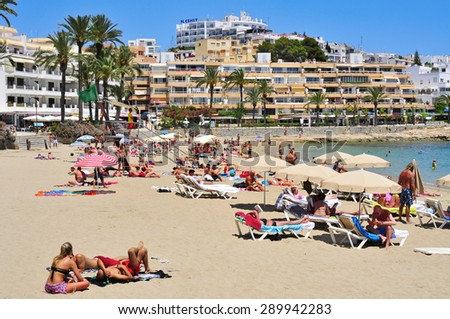IBIZA, SPAIN - JUNE 19: Sunbathers in the popular Ses Figueretes Beach on June 19, 2015, in Ibiza Town, Spain. Ibiza is a well-known summer tourist destination in Europe - stock photo