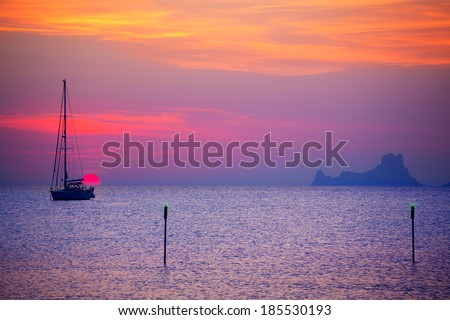 Ibiza sunset sun view from formentera Island with sailboat in Balearic Islands - stock photo