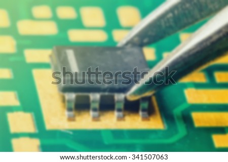 ic  pcb with pair of tweezers (blur) - stock photo