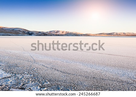 Ice and snow on the lake at sunset. Beautiful winter landscape  - stock photo