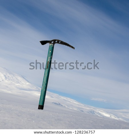 Ice axe with snow-capped mountain in the background - stock photo