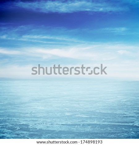 Ice big surface over the lake and blue sky - stock photo