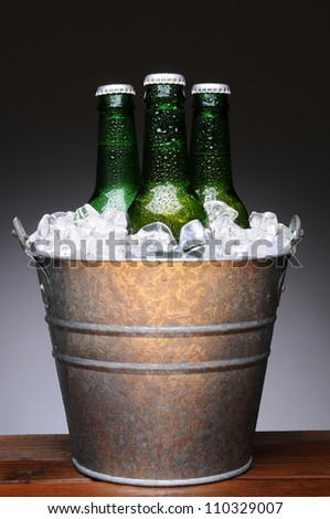 Ice bucket with three bottles of beer on a wet wood bar counter top. Vertical format on a light to dark gray background. - stock photo