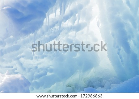 ice cave exit with icicles at sun light - stock photo
