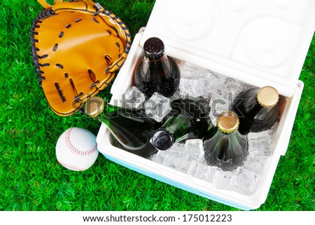 Ice chest full of drinks in bottles on grass background - stock photo