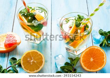 Ice citrus drink with lemon, orange, grapefruit and mint at blue. - stock photo
