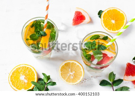 Ice citrus drink with lemon, orange, grapefruit and mint at white. - stock photo