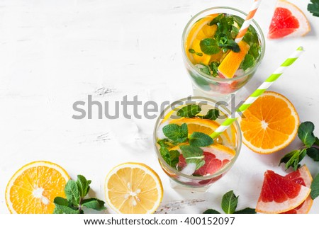 Ice citrus drink with lemon, orange, grapefruit and mint at white. Copy space. - stock photo