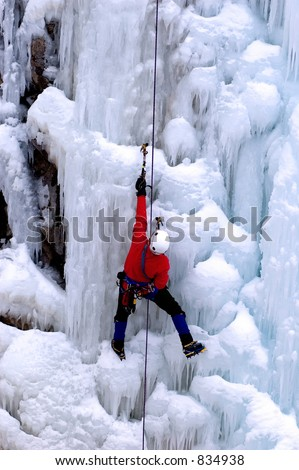 ice climber reaching for a higher ground - stock photo