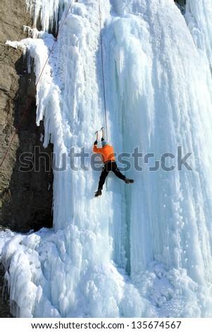 Ice climbing the waterfall. - stock photo