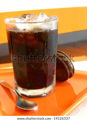 Ice coffee above an orange plate with yummy chocolate cookie - stock photo