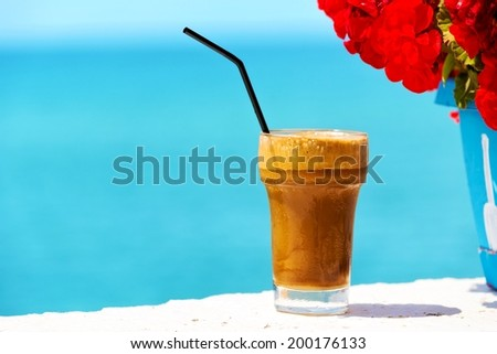 Ice coffee against sea background. - stock photo