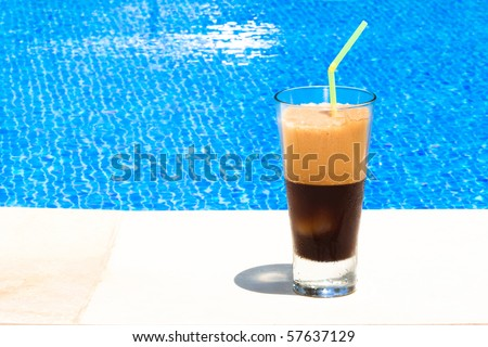 """Ice coffee (""""frappe"""") against blue clear water (swimming pool) - stock photo"""