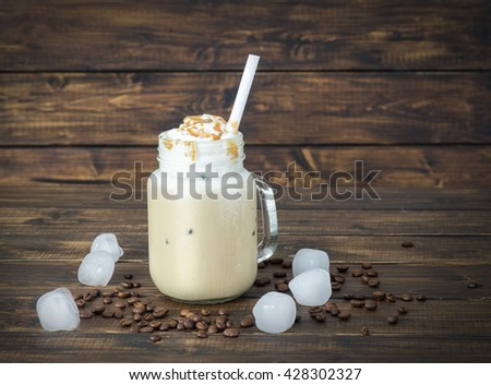 Ice coffee in a glass mug with drops of water on its surface  - stock photo