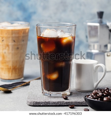 Ice coffee in a tall glass and coffee beans on a grey stone background - stock photo
