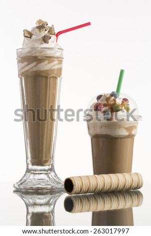 ice coffee in glass and plastic takeaway cup, decorated with whipping cream and bon-bons, advertisement for menu card - stock photo