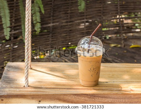 Ice coffee in plastic glass on old wooden table - stock photo
