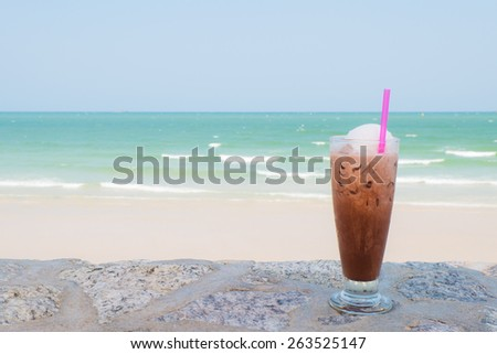ice coffee on the beach. Cold drink milk coffee with ice. Ice coffee in long glass, summer drink - stock photo